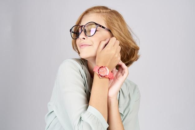 光の彼女の手にピンクの時計を持つファッショナブルな女性