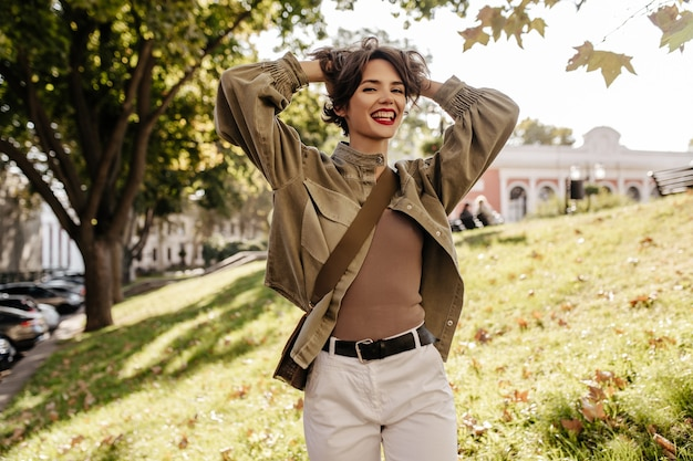 Fashionable woman with brunette hairstyle with handbag smiling outdoors. cool woman in olive jacket and white pants laughs outside.