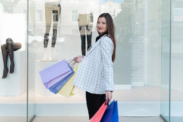 ショッピングモールで手にカラフルなパケットを持つファッショナブルな女性
