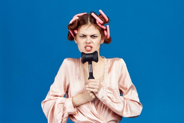 肉主婦を打つための彼女の頭のピンクのローブハンマーにカーラーでファッショナブルな女性