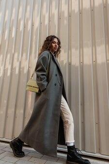 패션 가방과 신발이 달린 세련된 긴 코트에 곱슬머리를 한 세련된 여성이 금속 벽 근처를 걷습니다. 여성스러운 도시 스타일과 아름다움