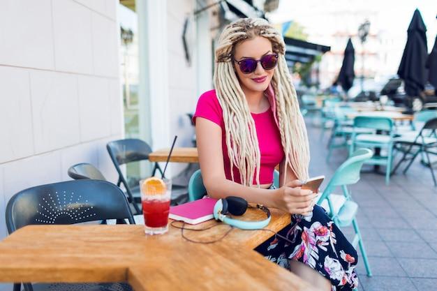 Модная женщина с дредами использует смартфон, публикует фотографии, читает новости и пьет вкусный розовый коктейль. в ярком летнем наряде. городское кафе.