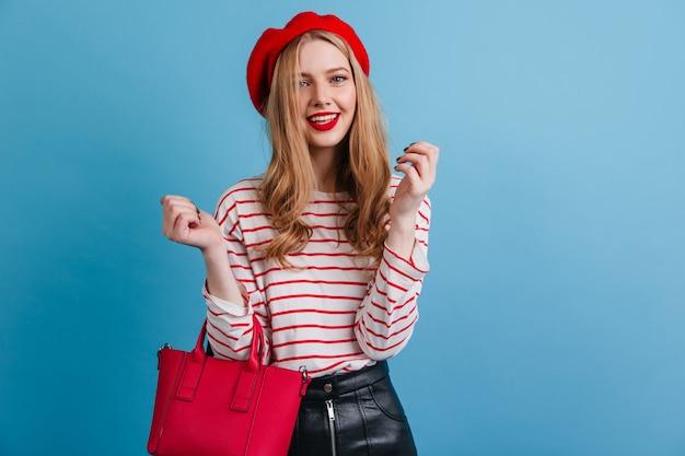 青い壁に立っているハンドバッグでファッショナブルな女性。フランスのベレー帽の遊び心のあるブロンドの女の子の正面図。