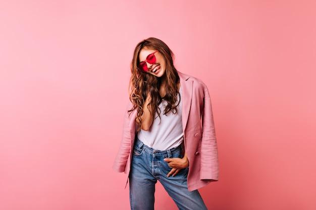長い生姜髪のファッショナブルな女性は幸せな笑い。トレンディなサングラスとピンクのジャケットで至福の白人の女の子の屋内の肖像画。