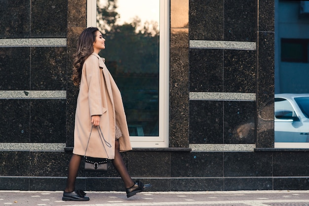 Fashionable woman with long hair walking in the city.
