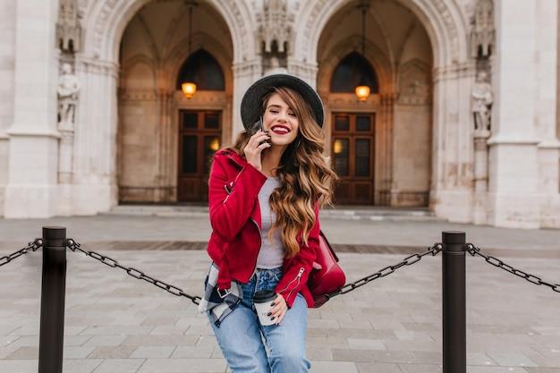 Donna alla moda con l'acconciatura lunga parlando al telefono vicino a un incredibile edificio storico nel fine settimana