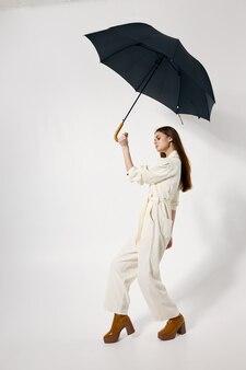 レインブラウンのブーツのモダンなスタイルから彼女の頭の保護の上に開いた傘を持つファッショナブルな女性