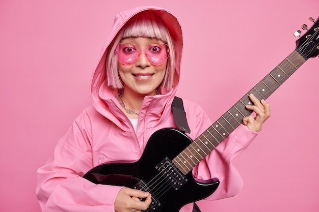Fashionable woman with pink hair pretends performing on stage plays rock and roll music wears heart shaped sunglasses and anorak poses indoor against rosy wall. talented female soloist