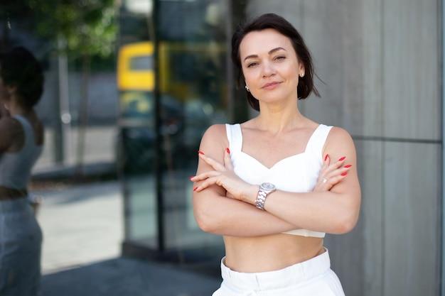 赤いマニキュアと腕時計を持ったファッショナブルな女性が腕を組んで、屋外のガラスの背景でカメラをのぞき込みます。クローズアップビジネスポートレート