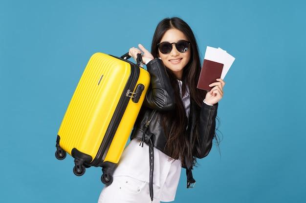 スーツケースパスポート飛行機のチケット旅行でファッショナブルな女性