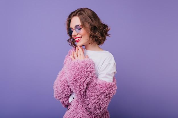 Donna alla moda con acconciatura ondulata sorridente con gli occhi chiusi. foto dell'interno del modello femminile entusiasta in giacca di pelliccia rosa.