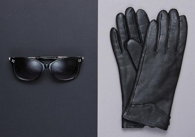 Модные женские аксессуары. солнцезащитные очки, кожаные черные перчатки. вид сверху, минимализм