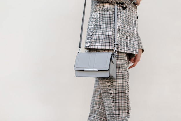 세련된 여성용 회색 세련된 핸드백. 확대. 체크 무늬 슈트와 최신 유행의 옷을 입고 세련된 어린 소녀