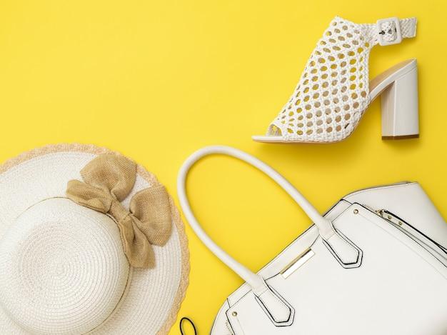 黄色の背景にファッショナブルな女性の帽子、バッグ、靴。女性のためのファッショナブルな服やアクセサリー。フラットレイ。