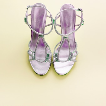 Fashionable women's sandals silver color on a yellow background.