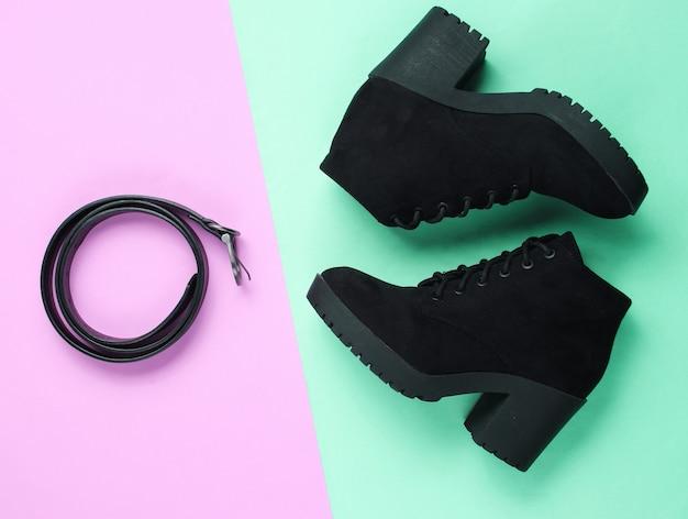 세련된 여성 신발 및 액세서리. 파스텔 배경에 부츠와 가죽 벨트. 평면도