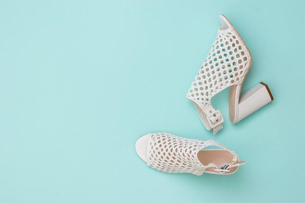 青に編みこみの白い革で作られたファッショナブルな女性の靴