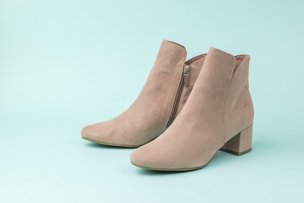 Fashionable women's suede ankle boots on a light turquoise surface