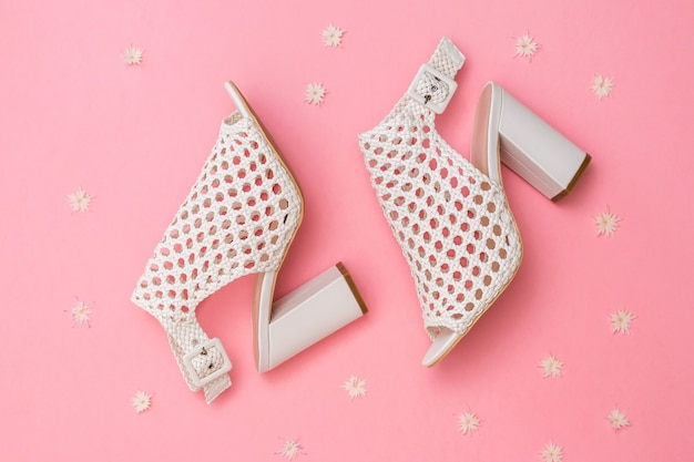 Fashionable women's summer shoes made of braided leather on a pink background with flowers. flat lay. the view from the top.