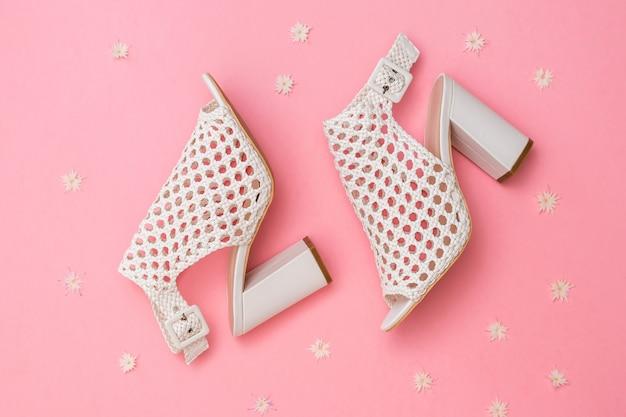 Модные женские летние туфли из плетеной кожи на розовом фоне с цветами. плоская планировка. вид сверху.