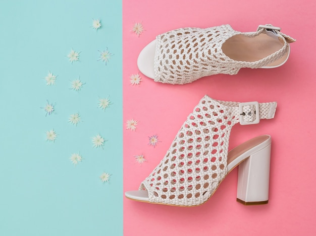 Fashionable women's white summer shoes with flowers on turquoise and pink surface