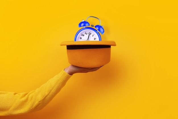 Fashionable yellow felt hat with blue clock in hand