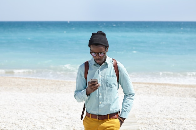 Fashionable young african american male tourist using mobile phone on desert beach, posting pictures of beautiful seascape around him via social media with azure ocean and blue sky in horizon