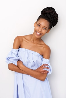 Fashionable young african woman standing with arms crosses against white background