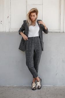 거리에서 벽 근처에 서 세련된 엄격한 회색 옷을 입고 유행 젊은 아름다운 모델 여자