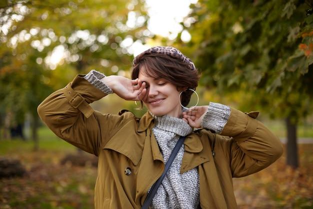 ファッショナブルな若い美しい短い髪のブルネットの女性は、彼女の顔に手を上げて、暖かい秋の日にぼやけた公園でポーズをとっている間、目を閉じて心地よく笑っています