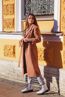 거리를 걷고 있는 갈색 코트를 입은 세련된 젊은 아름다운 세련된 여성. 웃고, 행복하고, 목적이 있는 여성을 위한 가을 패션 트렌드. 개념 스타일, 패션, 아름다움 및 성취 목표. 복사 공간