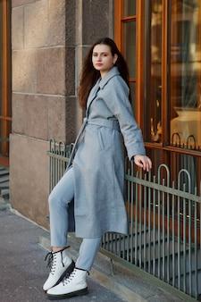거리에 걷는 회색 코트에 유행 젊은 아름 다운 세련 된 여자. 웃고, 행복하고, 목적이 있는 여성을 위한 가을 패션 트렌드. 개념 스타일, 패션, 아름다움 및 성취 목표. 복사 공간