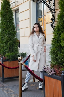 거리를 걷고 있는 흰색 코트를 입은 세련된 젊은 아름다운 세련된 여성. 웃고, 행복하고, 목적이 있는 여성을 위한 가을 패션 트렌드. 개념 스타일, 패션, 아름다움 및 성취 목표. 복사 공간