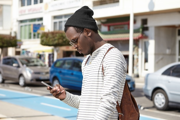 Fashionable young black man tourist with leather backpack looking at smartphone in his hands with serious expression, using online navigation app, searching for direction while got lost in big city