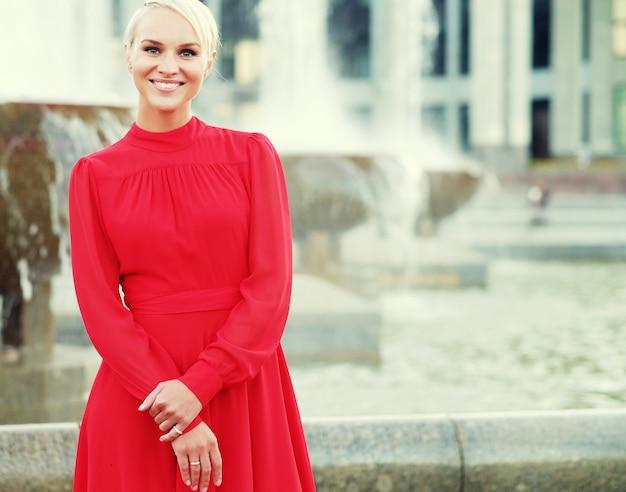 赤いドレスを着て、夏の日のファッショナブルな若いブロンドの女性