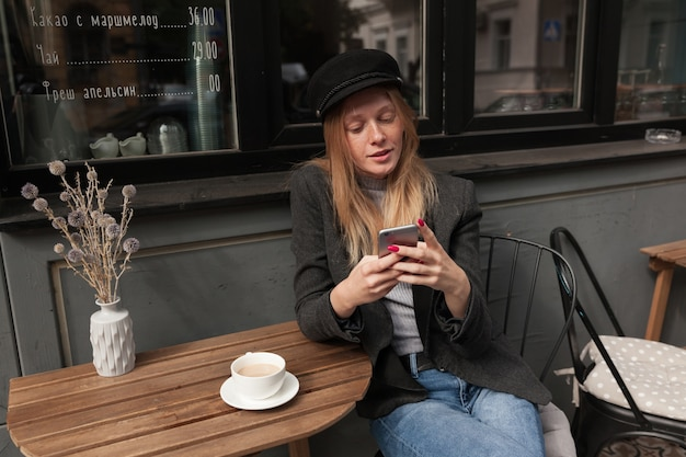Fashionable young blonde long haired woman in elegant clothes sitting at table over city cafe with mobile phone in raised hands, having cup of coffee and waiting for her bill