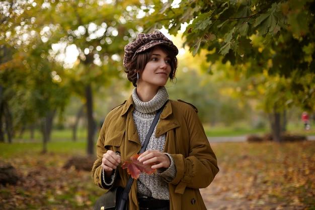 Giovane signora dai capelli castani alla moda con l'acconciatura bob che indossa vestiti caldi alla moda mentre cammina tra gli alberi gialli in una calda giornata autunnale, tenendo la foglia nelle mani alzate e sorridendo positivamente