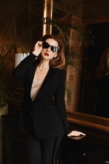 エレガントな黒のスーツと黒のサングラスでファッショナブルな若いビジネスレディ。美容、ファッション。光学およびアイウェア