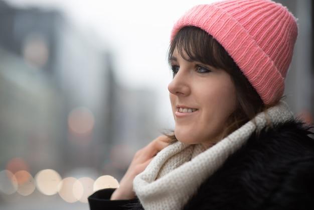 검은 코트를 입고 도시 거리와 가을 공원을 걷는 니트 모자를 쓴 세련된 젊은 사업가