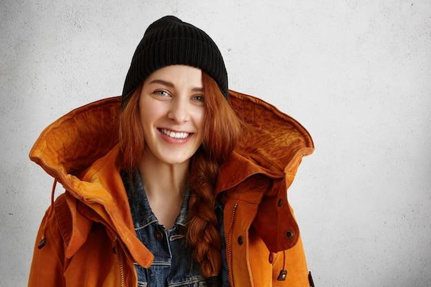 Модная молодая кавказская женщина в теплой одежде позирует в студии