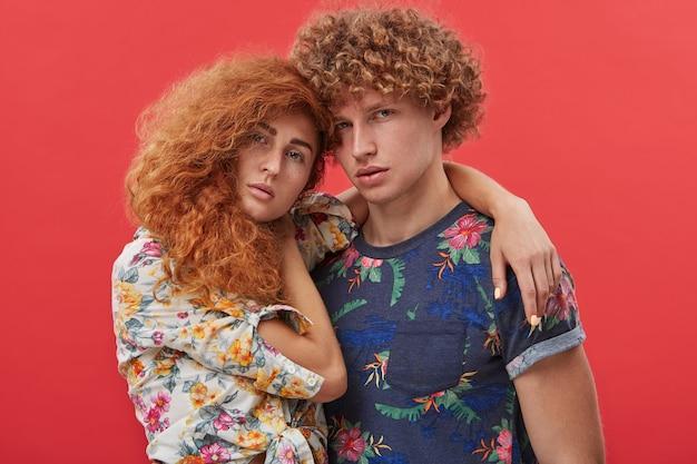 お互いをハグの花柄のトレンディな服を着たファッショナブルな若いカップル