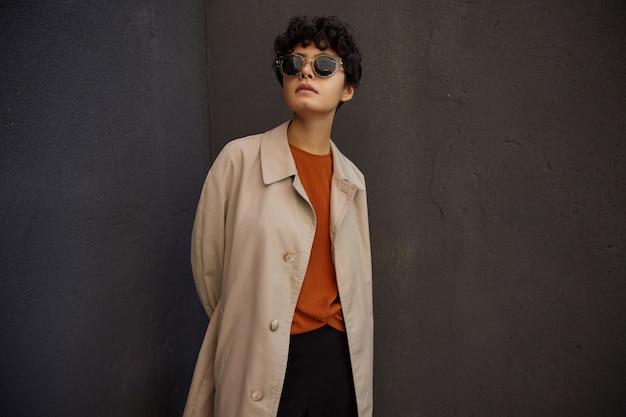 Bella donna dai capelli scuri giovane alla moda con taglio di capelli corto in piedi sopra il muro urbano nero e tenendo le mani dietro la schiena, indossando abiti alla moda e occhiali da sole