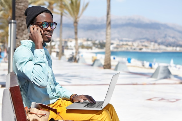 Fashionable young dark-skinned freelancer in hat and sunglasses having phone conversation on mobile while working remotely on laptop pc, sitting on bench in urban beach surroundings during holiday