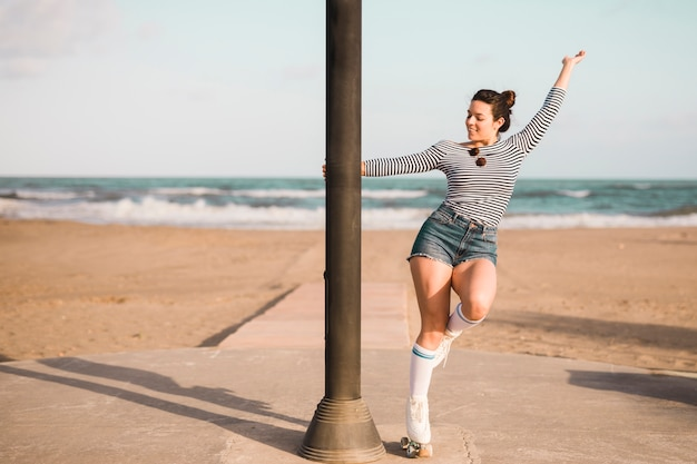 Fashionable young female skater holding pillar dancing at beach