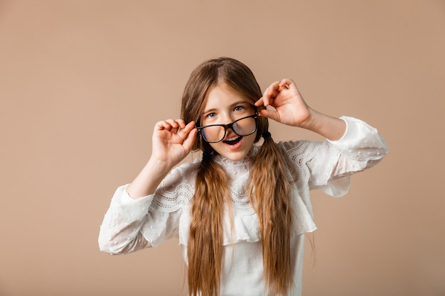 眼鏡をかけたファッショナブルな若い女の子、彼女はスタジオの背景に彼女の手で眼鏡を保持します