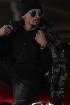 검은 코트를 입은 스타일의 선글라스를 쓴 세련된 젊은 힙스터 남자, 모자를 쓴 풀오버는 거리의 빨간 차 근처에 앉아 있다
