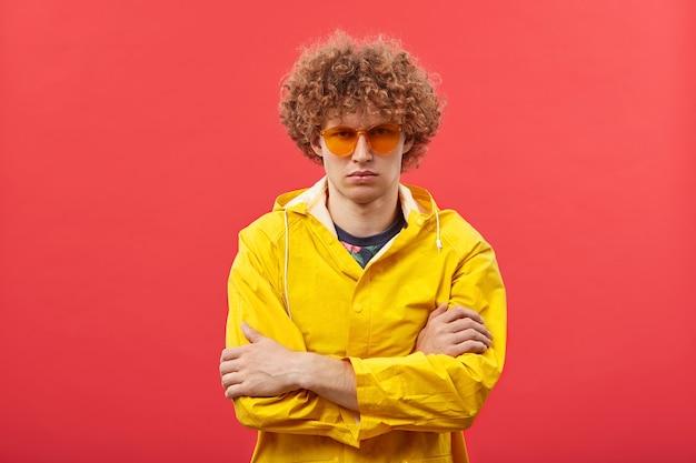 Модный молодой хипстерский мужчина с вьющимися рыжими волосами позирует