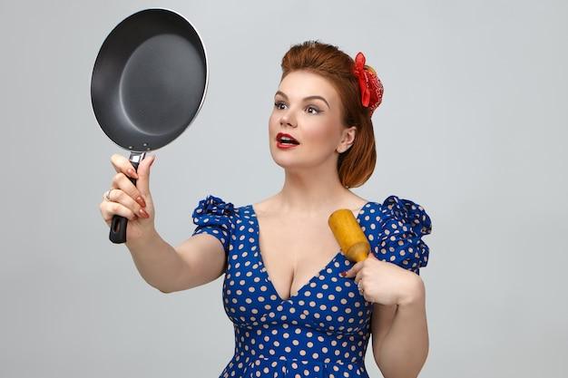 レトロなピンナップ衣装を着たファッショナブルな若い主婦が、乳棒または麺棒でスタジオでポーズをとり、フライパンにスティック防止コーティングを施しています。家事、キッチン、料理、食べ物、栄養