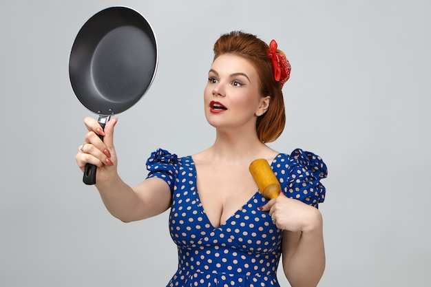 Fashionable young housewife dressed in retro pin up outfit posing in studio with pestle or rolling pin and frying pan with anti stick coating. housework, kitchen, cuisine, food and nutrition