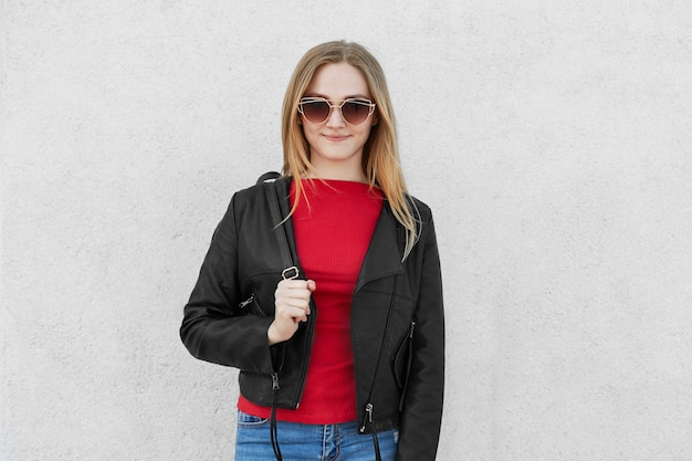 Fashionable young lady in big trendy sunglasses, red sweater, jeans and leather coat holding rucksack going for classes at university